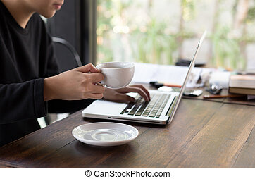 Student hand holding a coffee and using laptop