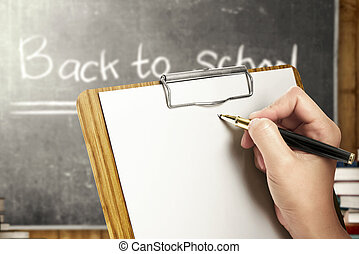 Student hands holding clipboard and writing in the classroom with piles of books and blackboard background