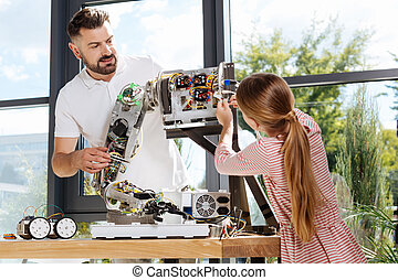 Student helping her teacher with robot arm construction