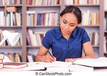 student, het bereiden, om te, de, exams., zeker, jonge, zwarte vrouw, schrijvende , iets, in, haar, opmerking blok, en, het boek van de lezing, terwijl, zittende , op, de, bibliotheek, bureau