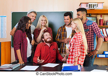 Student High School Group Laughing With Professor Sitting At Desk