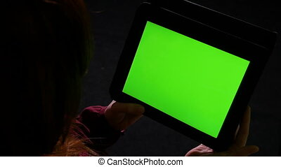 Student holding a tablet pc with green screen