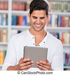 Student Holding Digital Tablet In Library