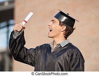 Excited male student holding diploma on graduation day in college