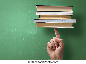 Student holding up books with A Finger
