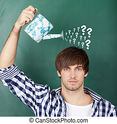 Student Holding Watering Can With Question Marks On Chalkboard