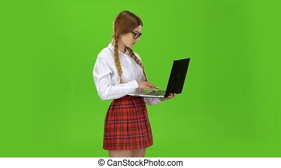 Student holds a laptop in her hands and prints on the keys....