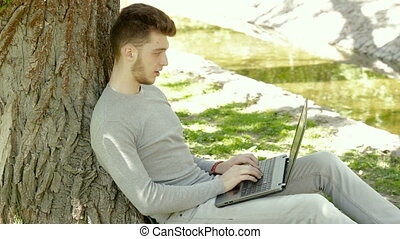 student in a park under a tree working with a laptop
