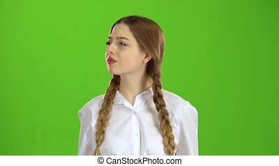 Student in a white blouse and pigtails shows a fis . Green...
