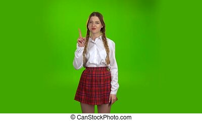 Student in a white blouse and pigtails shows a fist . Green screen
