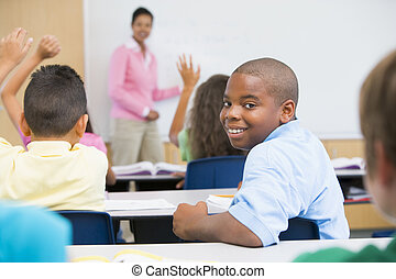 Student in class looking at camera with teacher in...