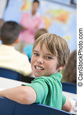 Student in class looking at camera with teacher in background (selective focus)