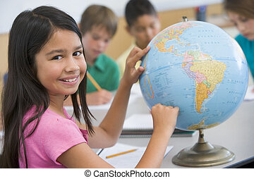 Student in class pointing at a globe (selective focus)