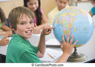 Student in class pointing at globe with students in...