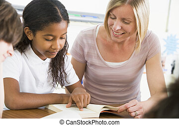 Student in class reading book with teacher