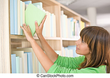 Student in library - happy woman choose book