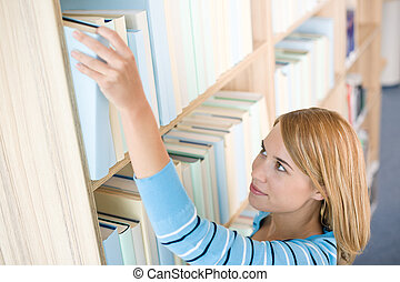 Student in library - happy woman reach for book