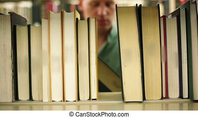 Student in library, pulling book off shelf