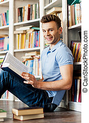 Student in library. Side view of handsome young man holding a book and smiling at camera while sitting on the floor and leaning at the library bookshelf