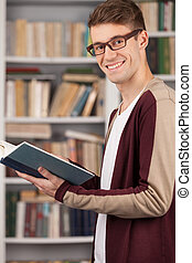 Student in library. Side view of young man reading a book and smiling while standing at the library