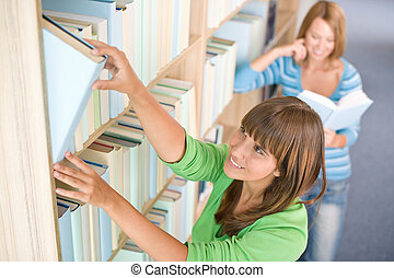 Student in library - two happy woman choose book