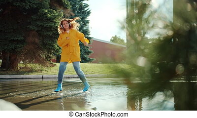 Student attractive redhead girl in raincoat and gumboots is jumping in puddle listening to music in headphones having fun. Lifestyle and emotions concept.