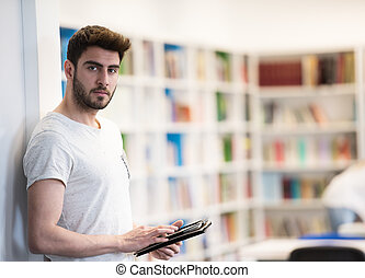 student in school library using tablet for research