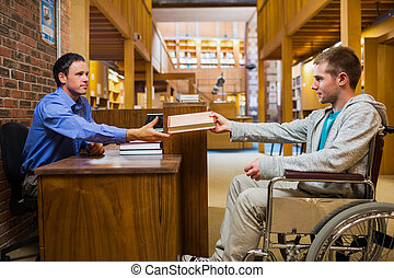 Student in wheelchair at the library counter - Side view of...