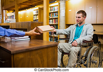 Male student in wheelchair at the counter in college library