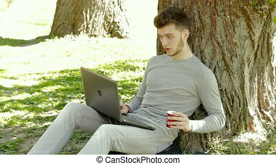 Student invigorates with a cup of coffee and works with laptop