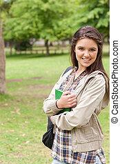 student, jonge, schoolboek, vasthouden, verticaal, het glimlachen
