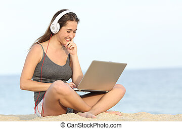 Student learning course with a laptop on the beach