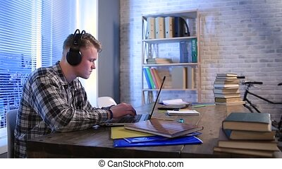 Student learning online with headphones and laptop -...