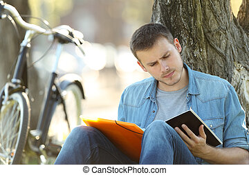 Student learning reading notes outside in a park