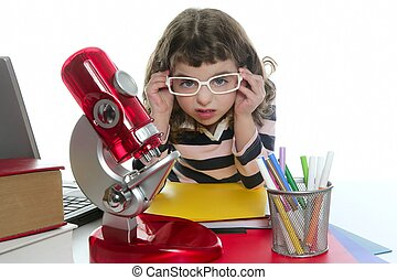 student little girl with microscope and laptop on desk white...