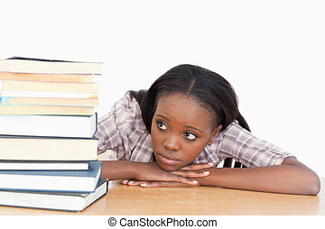 Student looking at a stack of books