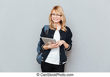 Student looking camera while using tablet