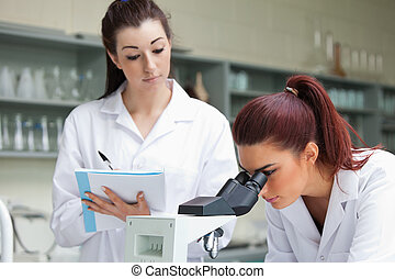 Student looking into a microscope while her classmate is taking notes in a laboratory