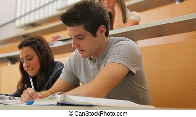 Student looking up from lecture and smiling while writing...