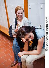 Student making fun of her classmate in a corridor