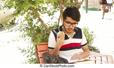 Student man learning and eating cakes sitting in the park