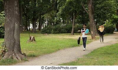 Student man walking in the park in summer day