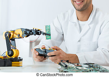 Student of technology using a modern robotic arm