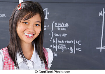 Student pose in front of blackboard