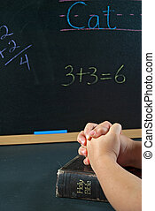 student praying in school - Little hands folded in prayer on...