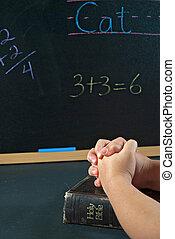 student praying in school - Little hands folded in prayer on...