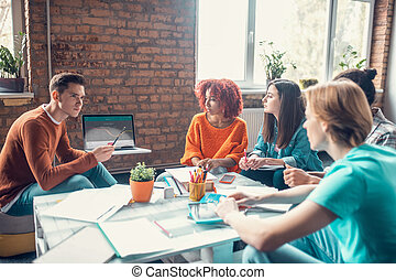 Student presenting his ideas with friends while having group project