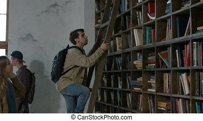 Student reaching to book in bookshelf using ladder