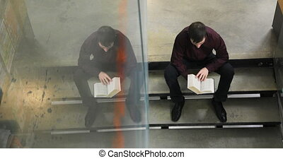 Student reading a book in the library. Concept: educational,...