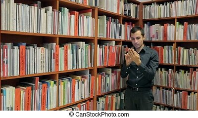 Student Reading a Book in the Library on Phone